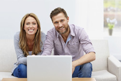 Young couple in living room with a laptop